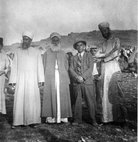 Schwarz-weiß-Foto von vier Männern in wüstenartiger Landschaft, einer mit Anzug, Krawatte und Hut, drei mit langen Bärten und Gewändern