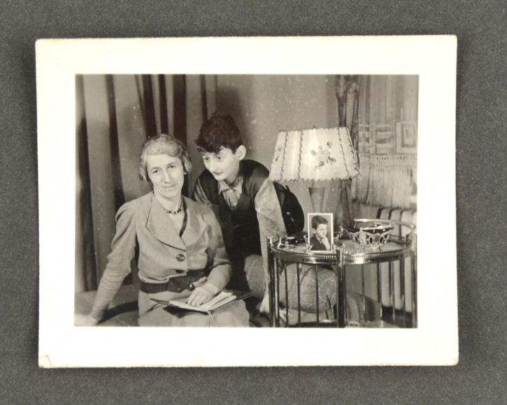 Eine Frau und ein Kind neben einem Tischchen mit Stehlampe, auf dem Tisch steht ein Fotoporträt eines Jungen