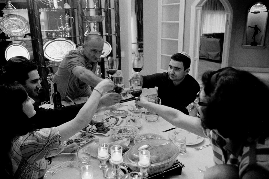 Black and white photograph of a group of people sitting at a dinner table with lots of food, they all raise their wine glasses in the middle of the table, the men are wearing Kippahs