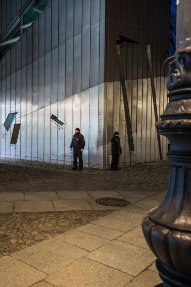 A policeman and a policewoman stand in front of the museum, looking in different directions.