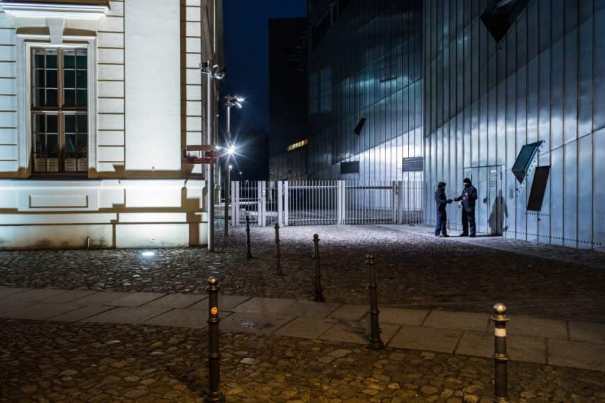 Two police*women standing in front of the Libeskind-Building at night, talking.