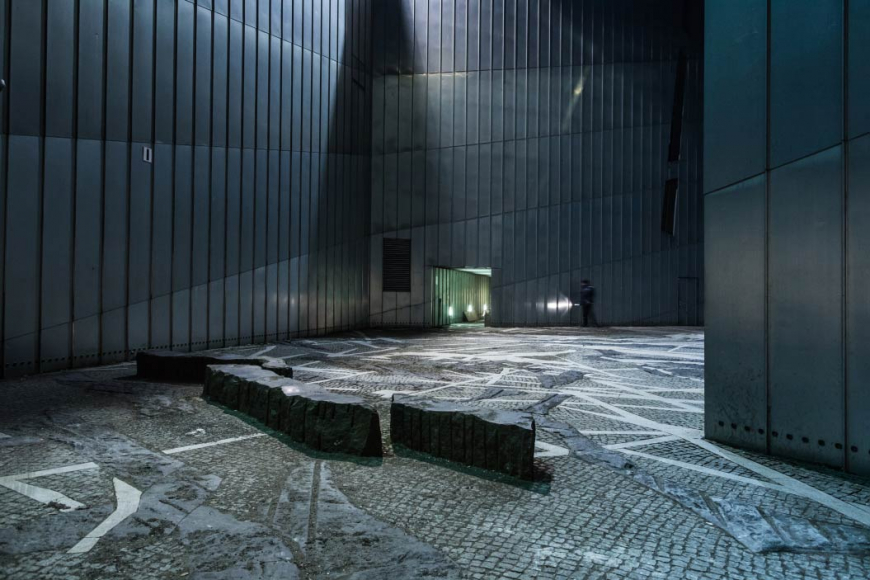 A view of the Paul-Celan-Hof of the Jewish Museum Berlin with a policeman walking along the far wall.