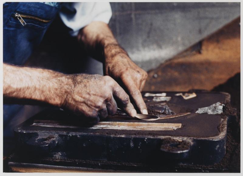 Der Gießer Herr Ehrlich fertigt eine Gussform aus dunklem Sand
