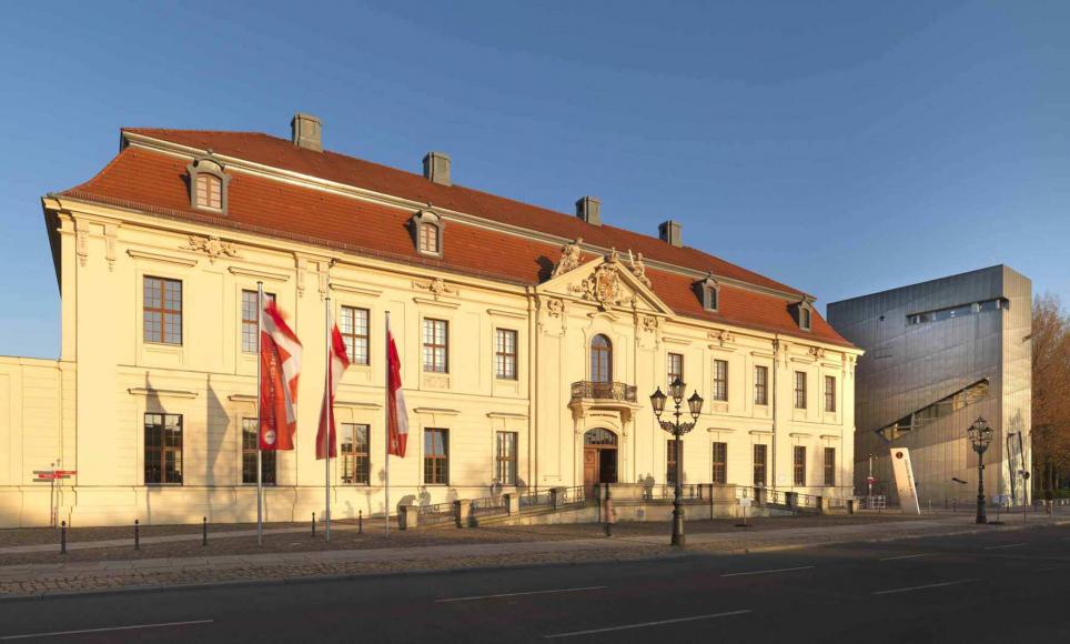 Edificio d'epoca del Museo Ebraico di Berlino al crepuscolo, con tre bandiere