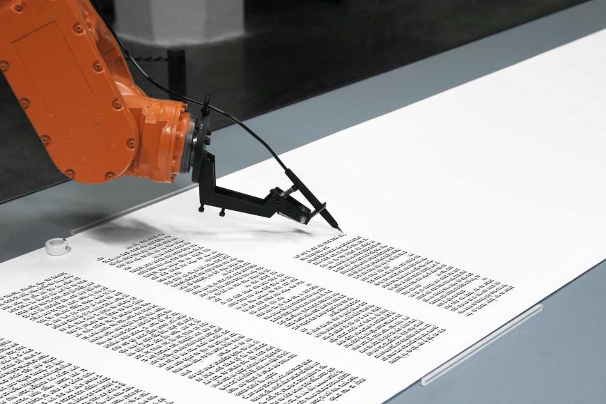 Ein Roboterarm hält eine Tintenfeder und schreibt hebräische Schriftzeichen auf eine lange Papierrolle