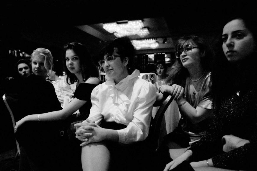 Black and white photograph of a group of nicely dressed women sitting in a large room with their hands in their lap, they are focused on something in the distance