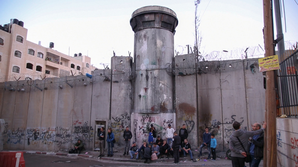 The threatening-looking security barrier made of concrete components with watch tower and barbed wire, and a few people sitting or standing in front of the wall