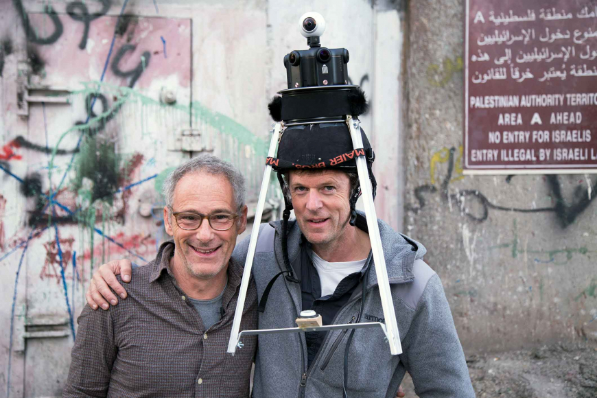 Dani Levy and Filip Zumbrunn embrace; Zumbrunn is wearing a camera with a tripod on his head