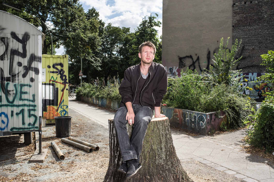 Photo: a man sitting on a tree trunk in front of trees and trailers sprayed with graffiti