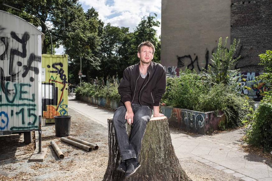 Foto: Ein Mann, vor Bäumen und mit Graffiti besprühten Containern auf einem Baumstamm sitzend