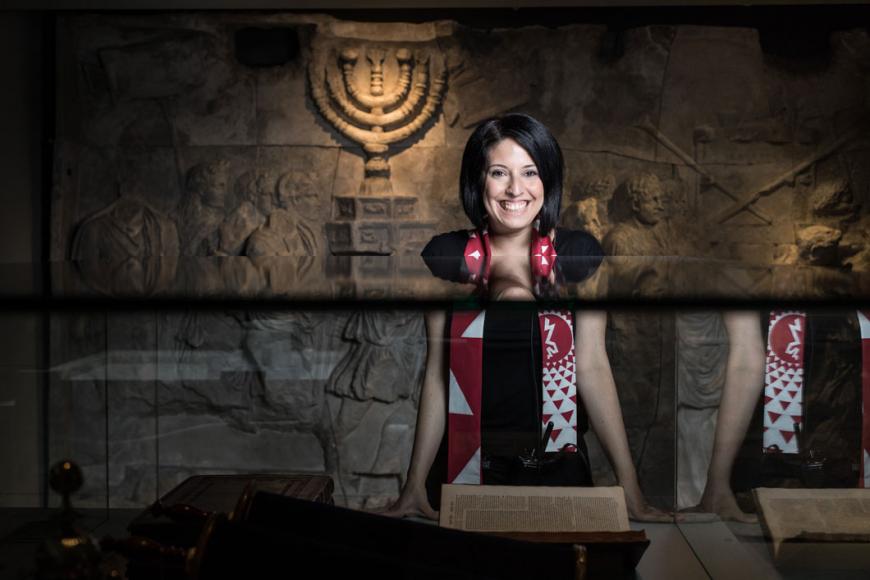 Eine lachende Frau steht in einem Raum der Ausstellung Welcome to Jerusalem