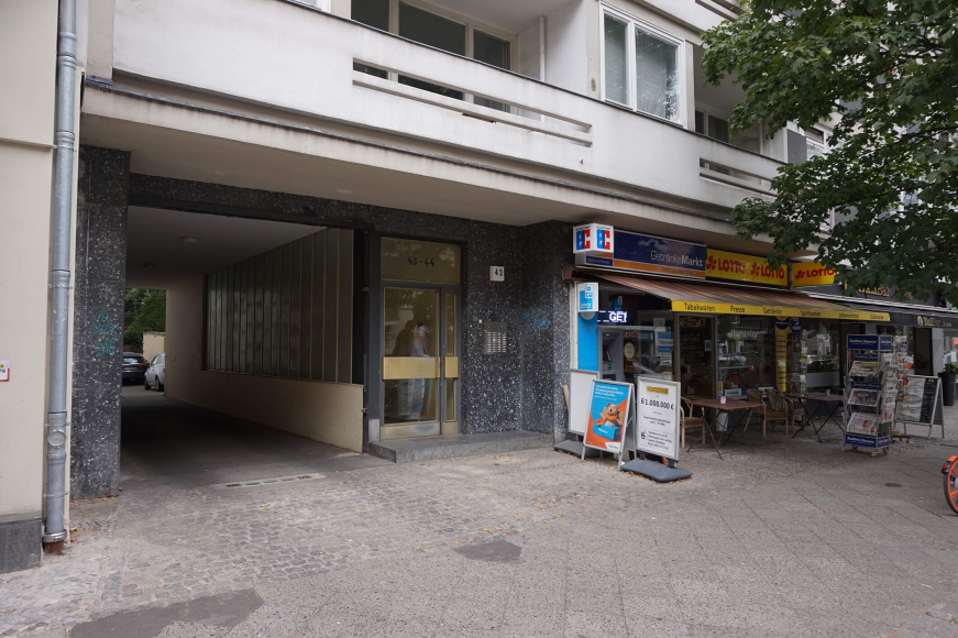 Color photo: Ground floor of a postwar building showing passageway, front door, and convenient store