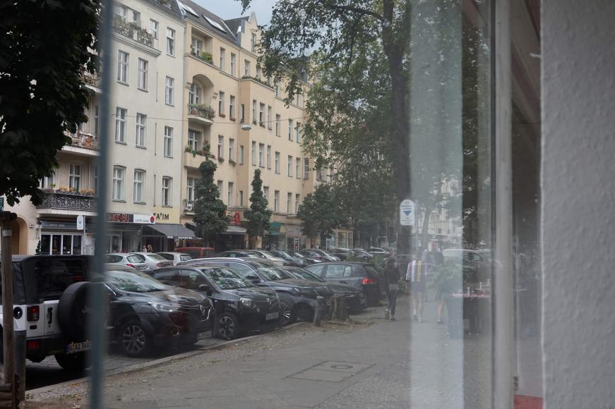 Color photo: View through storefront of prewar Berlin apartment buildings
