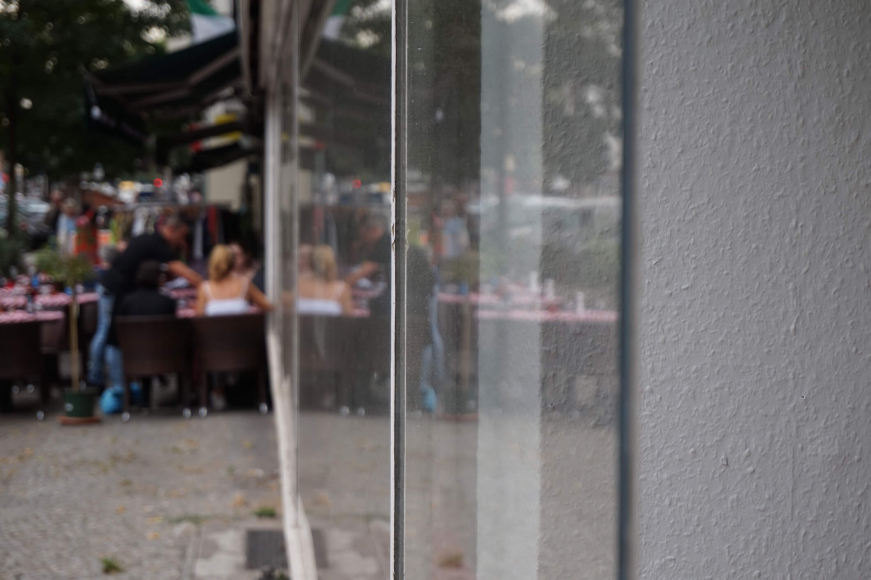 Color photo: View along a storefront showing people at a restaurant in the background