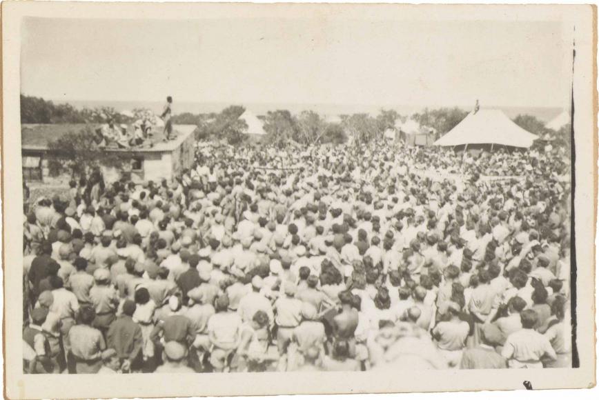 Auf dem von schräg oben fotografierten Schwarzweißbild ist eine große Menschenmenge einem Haus zugewandt, auf dessen Dach ein Mann steht und zur Menge spricht.