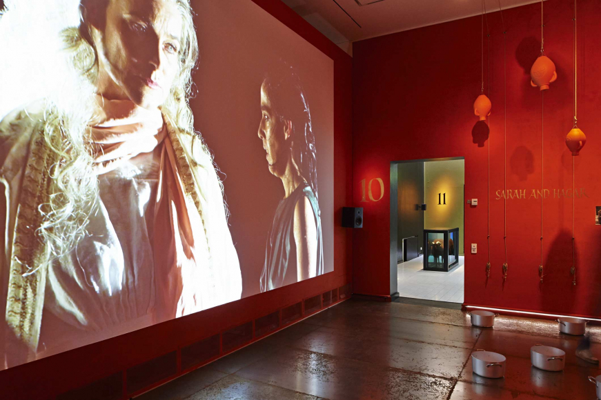 A red room with one wall covered by a giant projector screen, the screen is showing an image of two women