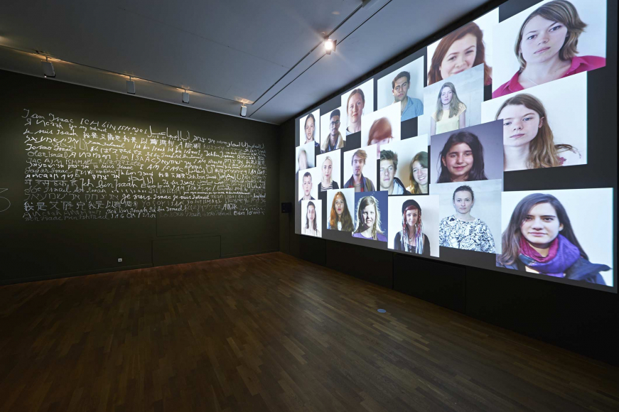 An empty room facing two walls, one wall is covered in portrait photos, the other wall is covered in text of various languages