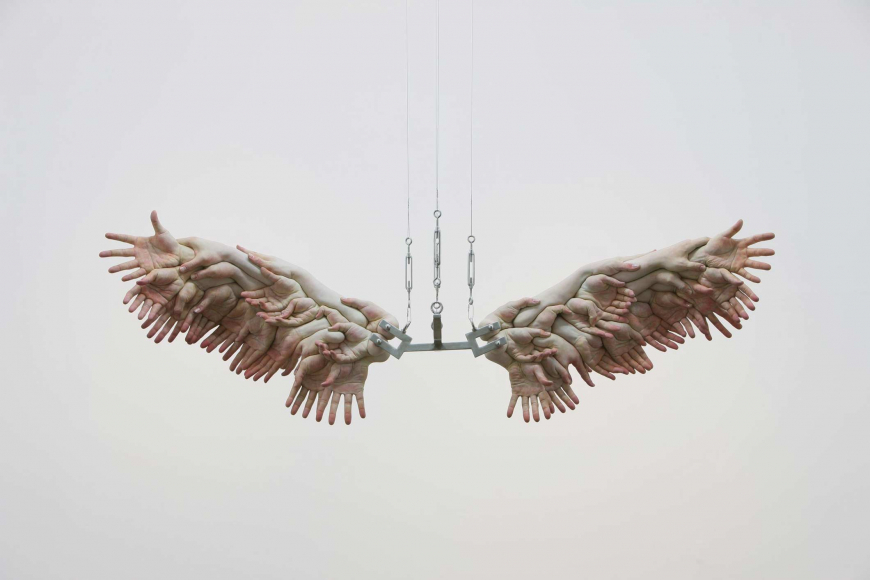 Floating sculpture of decapitated fleshy white hands and arms form together to create an replica of feathered wings