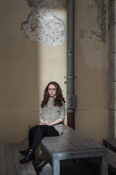 Foto: Frau, vor Hauswand mit abbröckelndem Putz auf einem Holztisch sitzend