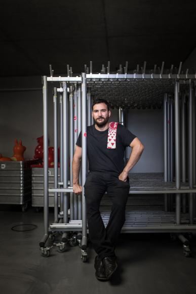 Ein jüngerer Mann sitzt auf einem leeren Garderobenständer