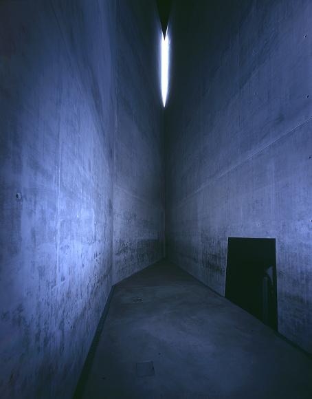 Une pièce étroite avec de hauts murs gris en béton.
