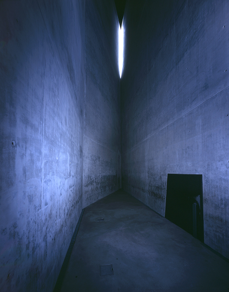 Una stanza stretta con pareti grige e alte in cemento.