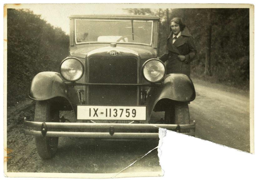 Schwarz-weiß-Foto einer jungen Frau in winterlicher Kleidung neben einem Auto auf einer Landstraße, die rechte untere Ecke der Fotografie ist ausgerissen.
