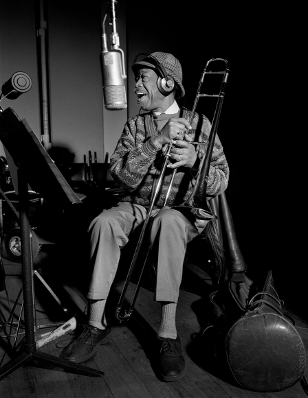 Al Grey with a trombone in his hands in the recording studio and sings into the microphone