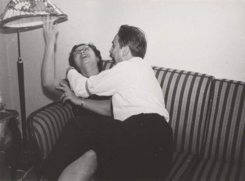 Eine Frau und ein Mann scherzen auf einem gestreiften Sofa unter einem Lampenschirm