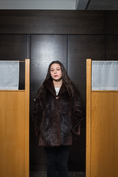 Photo: a woman in a fur coat in front of a dark veneer panel