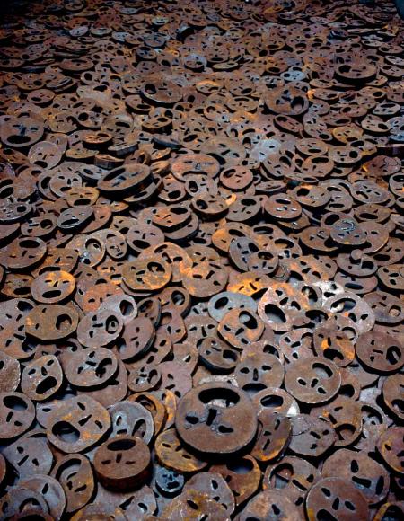 Meer von Gesichtern aus Eisenplatten mit aufgerissenen Mündern