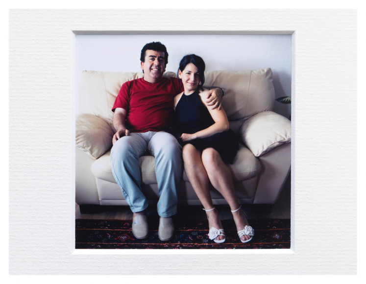 A woman and a man sit on a small couch and smile at the camera, the man has his arm around the woman's shoulders