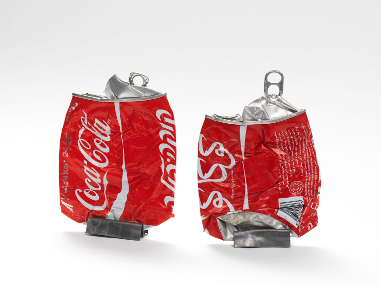 Two flattened red aluminum soda cans displayed vertically by two metallic clips