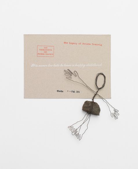 A small wire sculpture attached to a small stone depicting a human figure next to a tan card with text on it