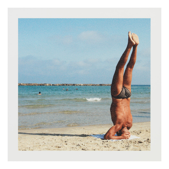 Vintage photograph of the back of a muscular, tan, older man doing a handstand by the shore of a beach
