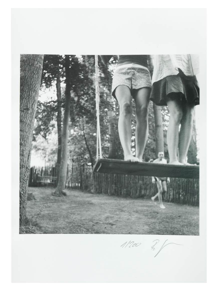 A black and white photo of two girls standing on a wide wooden swing. Only their legs are visible