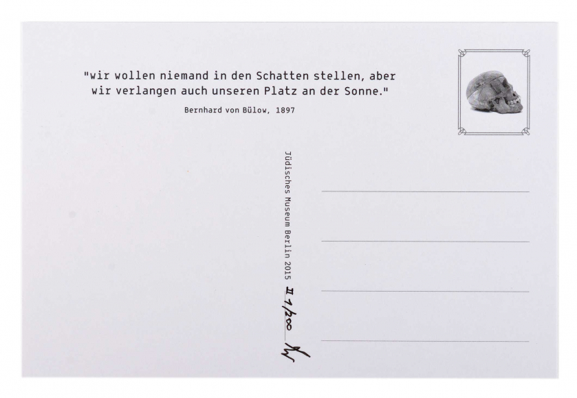 The back of a white unfilled postcard, there is a quote on the top an a picture of a skull where the postage stamp should be