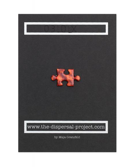 In der Mitte einer schwarzen Montagepappe wurde mit rotem Faden ein Puzzlestück aus bedrucktem Fotokarton aufgenäht.