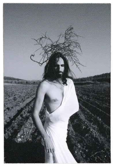 Foto: Im Vordergrund steht ein Mann vor einem brachen Feld mit tiefen Pflugfurchen eng umhüllt von einem weißen Tuch mit halbseitig freiem Oberkörper und langen dunklen Haaren. Über dem Kopf befindet sich eine Art Gestrüpp in Anlehnung an die Dornenkrone.