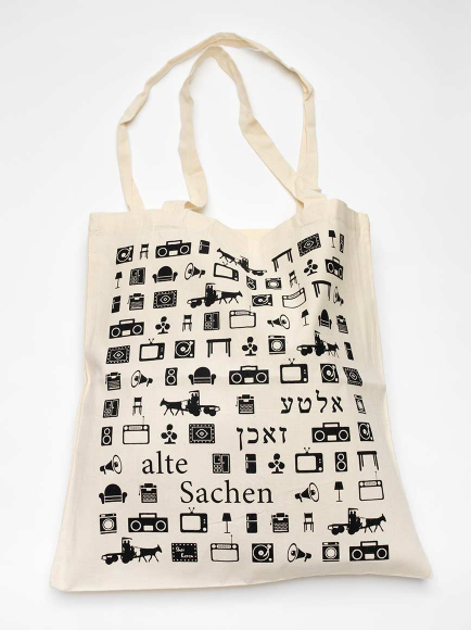 "Canvas bag covered in pictograms of furniture, boom boxes, megaphones, horse-drawn carriages, and the label ""alte Sachen,"" meaning ""old things,"" in German and Yiddish"