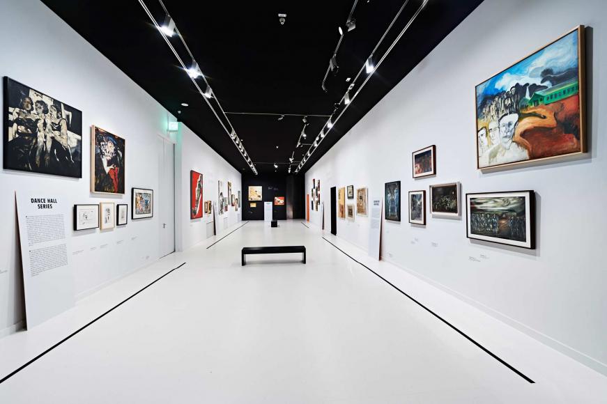 Blick in einen weiß gehaltenen Ausstellungsraum mit Bildern an den Wänden