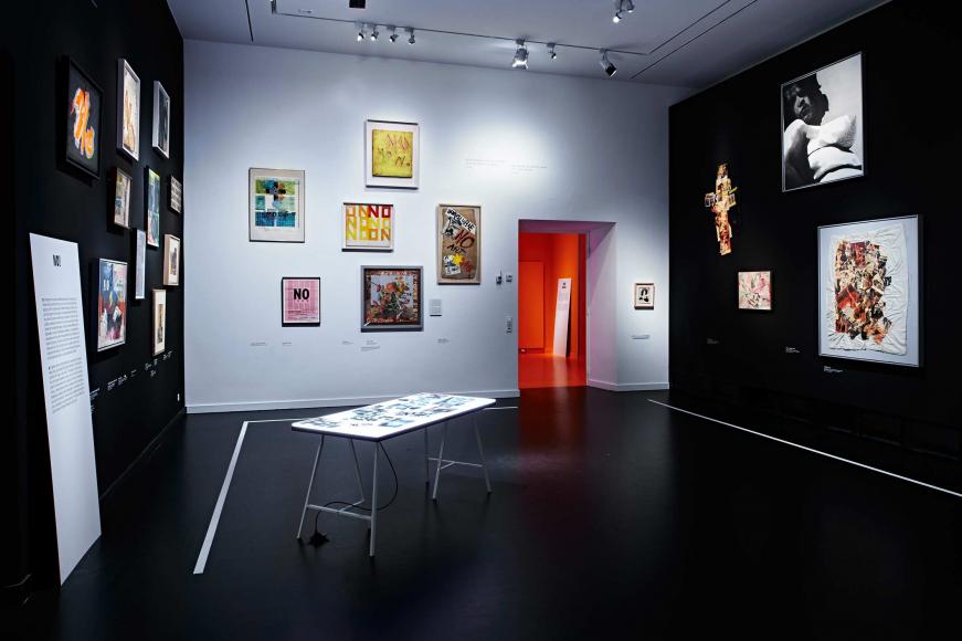 Ein schwarz-weiß gehaltener Ausstellungsraum mit Bildern an den Wänden und einem Tisch mit Fotos in der Mitte
