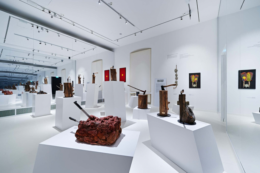 Exhibit space of sculptures of various material like wood or stone with axes and knifes stuck in them