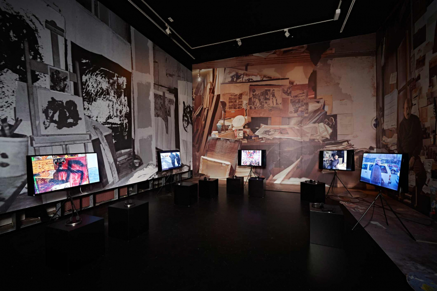 Exhibition space, the walls are covered with large photographs of Boris Lurie's studio, TV screens fill the room