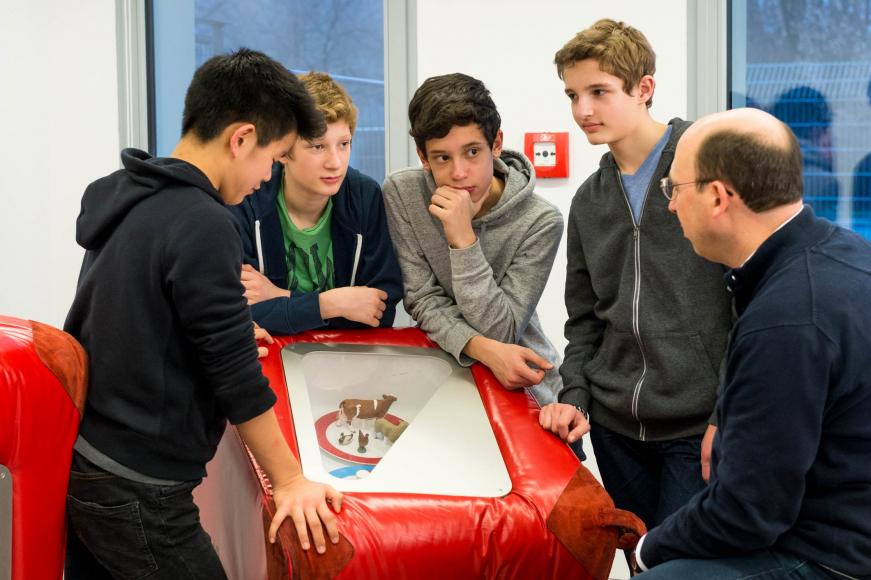 on.tour-guide erklärt Schüler*innen die mobile Ausstellung