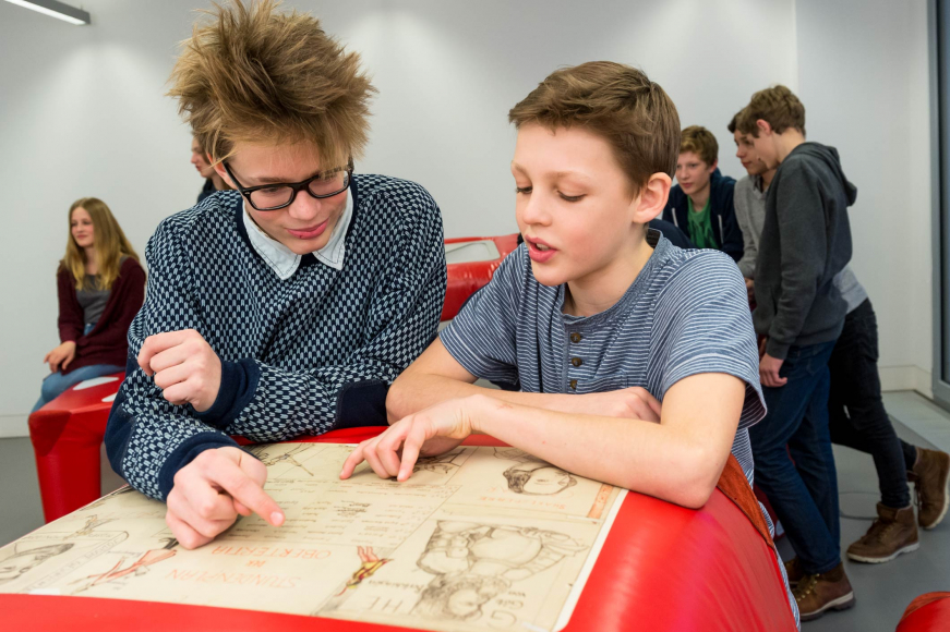 Two boys studying an old class schedule