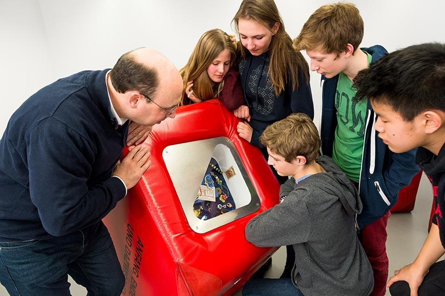 Ein Museumsguide zeigt Schülern einen Ausstellungswürfel