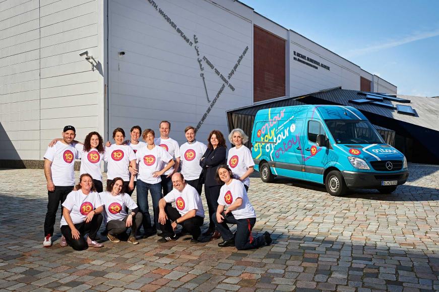 Mitarbeiterinnen und Guides von on.tour vor einem on.tour-Bus