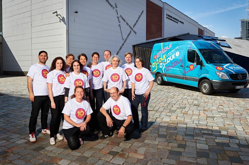 Mitarbeiter*innen und Guides von on.tour vor einem on.tour-Bus