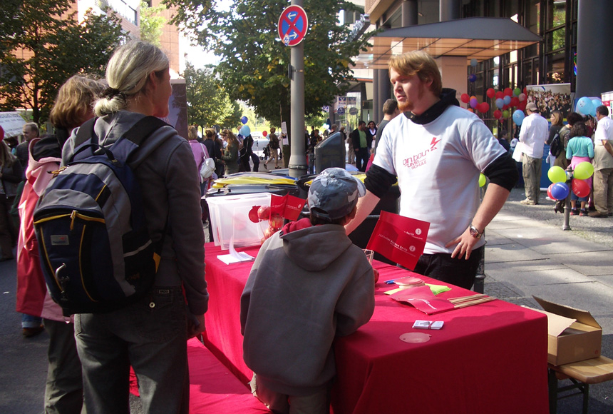 Visitors of the children's day talk to an employee at an on.tour stand.